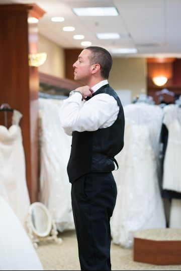 The groom trying on suits