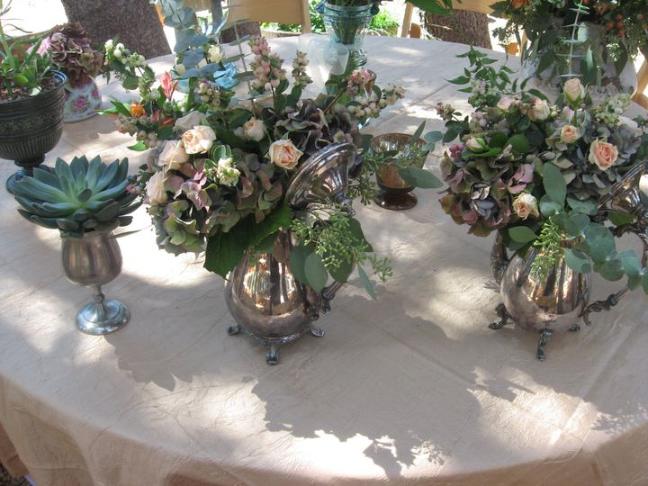 Vintage containers with hydrangeas and spray roses for dessert tables