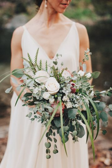 Rustic, cascading bridal bouquet with protea, roses and eucalyptus.