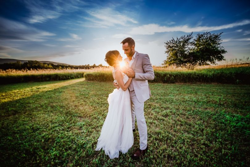 Couple posing in a field at sunset