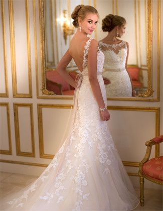 This Lace and Tulle fit-and-flare designer gown from the Stella York collection features an illusion...