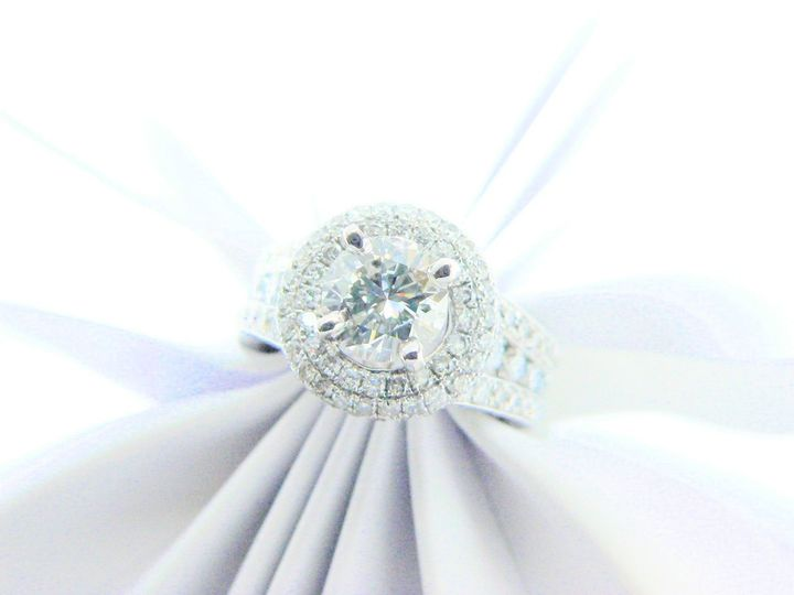 Halo diamond engagement ring with round diamond center stone and round diamond accent stones.