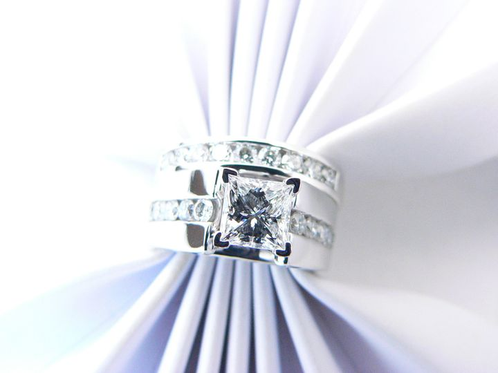 Princess cut diamond center stone with round diamond accent stones on white gold.