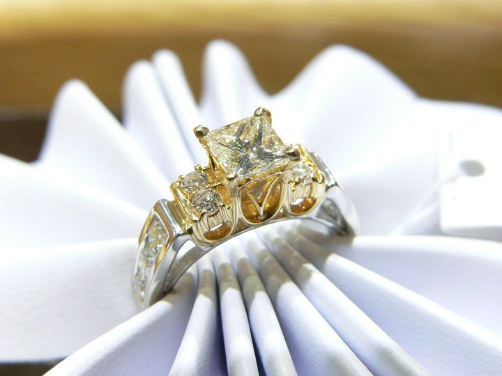 Platinum and 18 karat yellow gold diamond engagement ring with princess cut center stone. Round...
