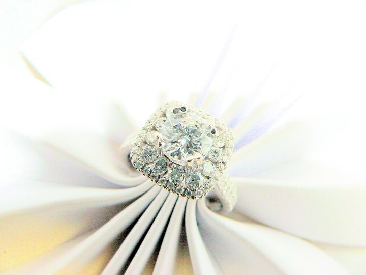 White gold diamond Halo style diamond engagement ring. With round diamond center stone and round...
