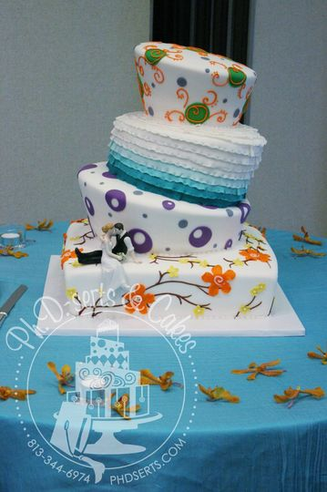 A large topsy turvy wedding cake with many colors and themes all joined together into one cohesive...