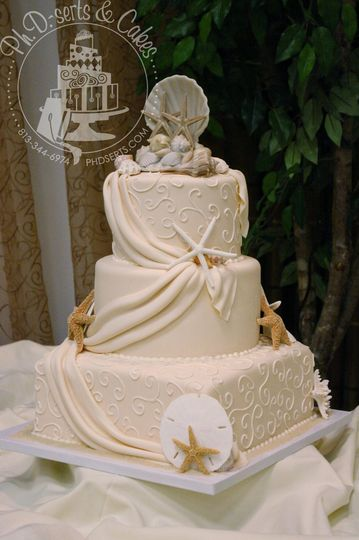 Elegant, ivory seashell wedding cake with real shells, fondant drapes, and hand-piped buttercream...