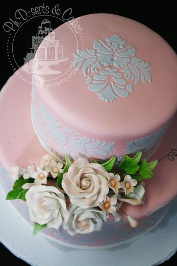 Gorgeous wedding cake covered in light pink fondant and adorned with gray damask stenciling.  Floral...