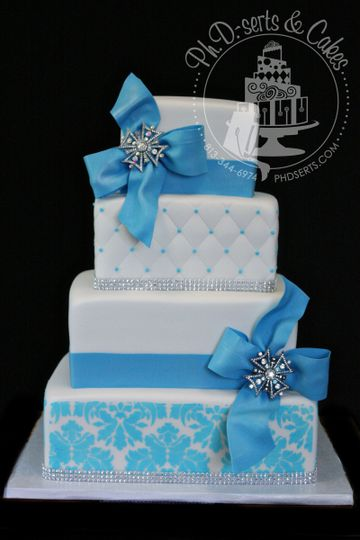 Fondant-covered square wedding cake with blue Damask, quilting, and large romantic blue bows....