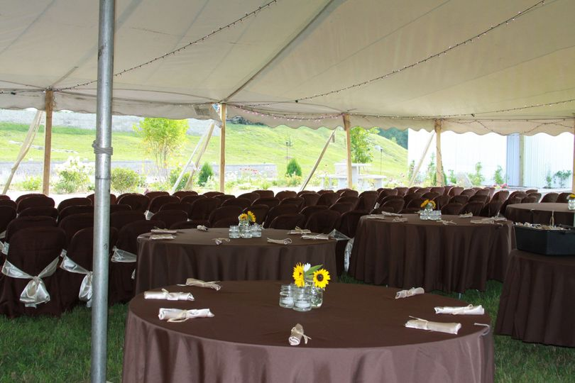 Seating for guests under tent during ceremony.  Chairs are then set around tables for drinks and...