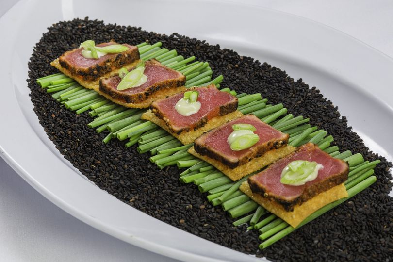 Seared tuna tataki with shaved scallions and wasabi foam on a wonton plank