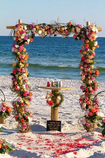 Barefoot Weddings bamboo arbor wrapped in grapevine smothered in fresh roses