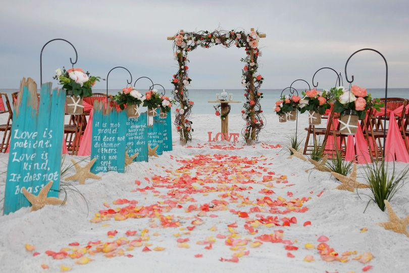 Barefoot Bliss beach wedding package in Destin Florida features our bamboo arbor wrapped in...