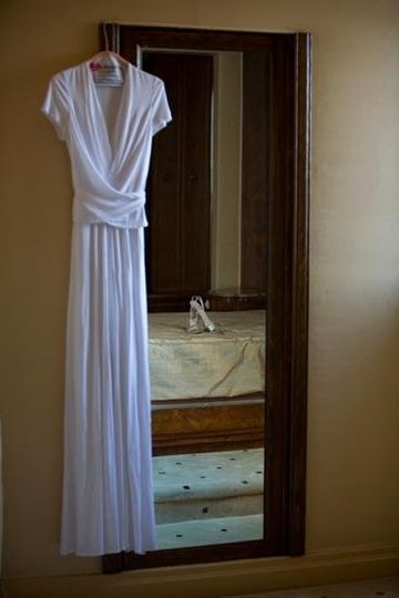 Wedding dress hung next to mirror with shoes in background.
