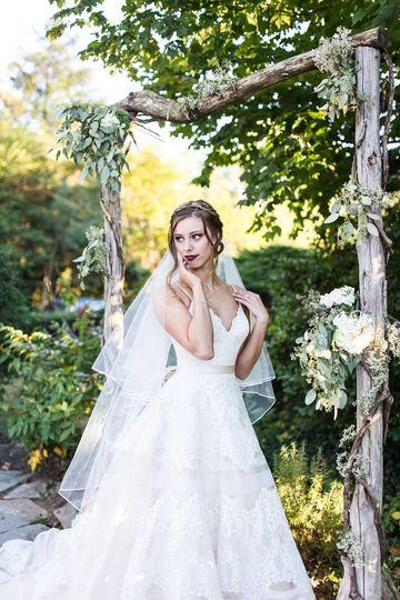Bride poses under arch