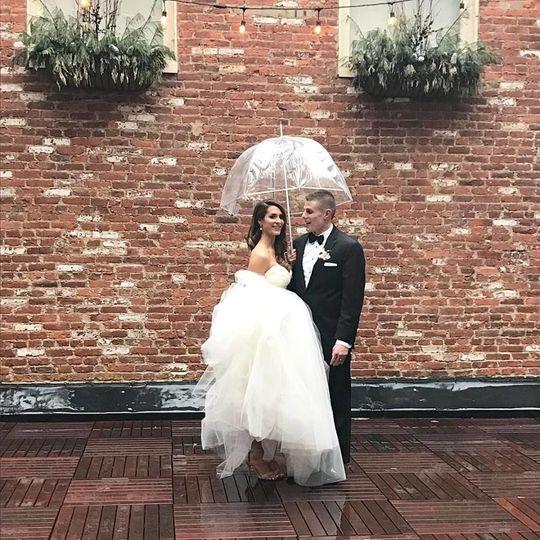 Newlyweds sharing an umbrella