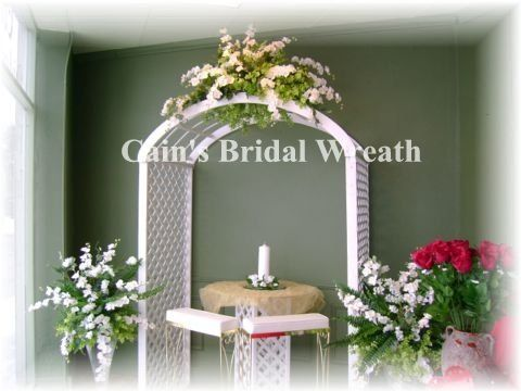Wooden White Lattice Arch with white and soft green flowers. Two glass matching side arrangements