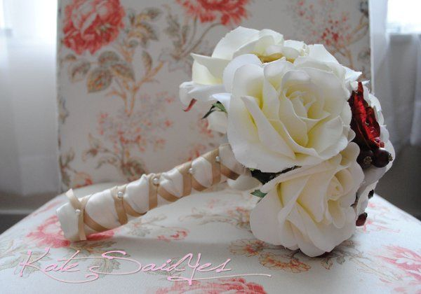 A beautiful white rose bouquet, accented with red and cream roses, and deep red berries. This...