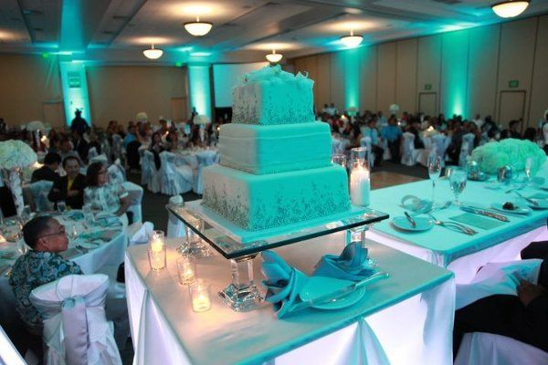 Beautiful glass elevated 3 tier wedding cake with Tiffany Blue Uplighting