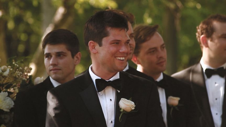 grooms face bride walking down aisle