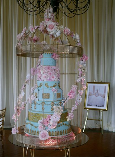 Marie Antoinette inspired cake under a 6 foot tall golden birdcage. The cake and cage is covered...