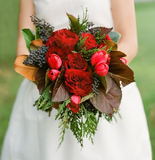 Red cabbage roses, hydrangea leaves, red tulips, and red berry were used to create this bouquet....