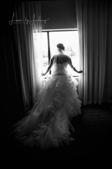 Bride looking at the window after getting dressed in her wedding gown