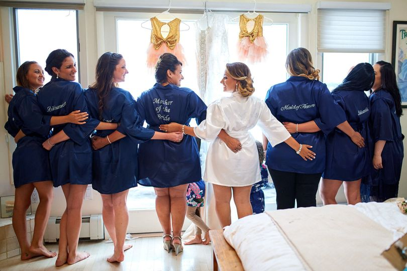 Bride with bridesmaids and mother wearing robes