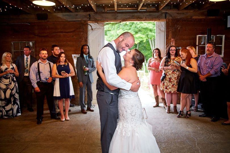 Bride and groom have their first dance at their rustic barn wedding reception