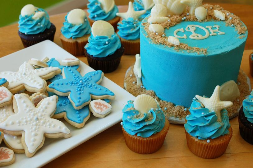 Teal beach-themed wedding cake with cupcakes and cookies