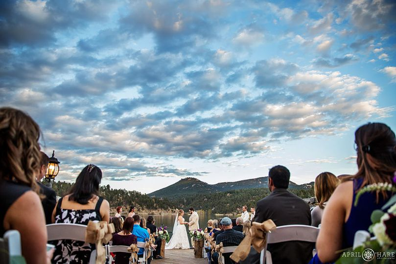 Ceremony on water's edge with blue sky and clouds