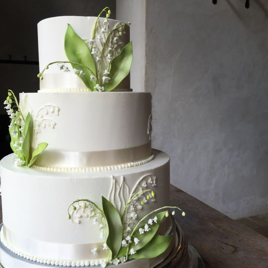 Three tier white wedding cake with leaves