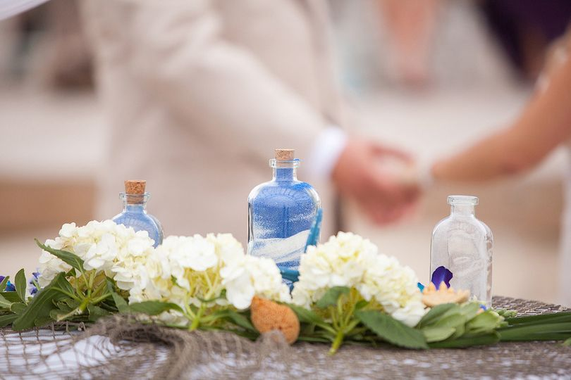 blue and white sand ceremony jars on beach outer b