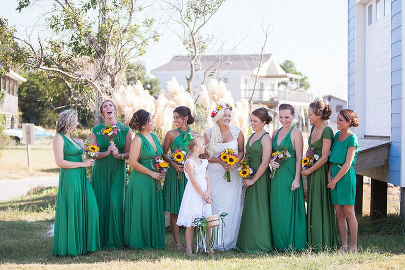 bride and bridesmaids with flower girl laughing