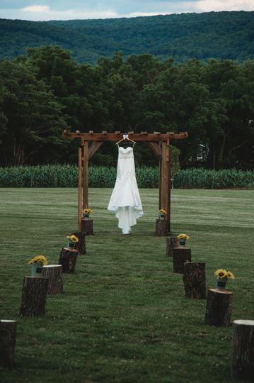 Wedding dress hanging on wooden arch