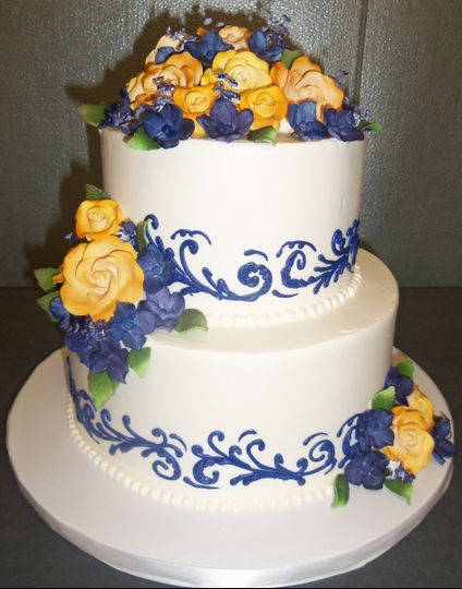 White cake with blue patterns and yellow roses