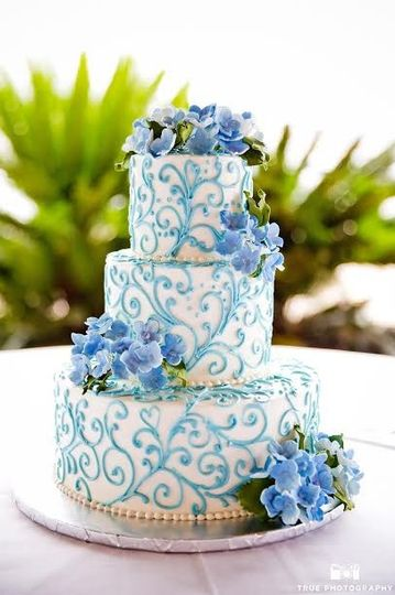 Three tier white and blue cake with embellishments