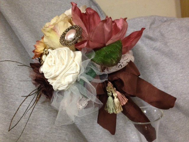 Side view of chocolate brown satin wrapped handle with antique light rose pink lace...satin tassels...
