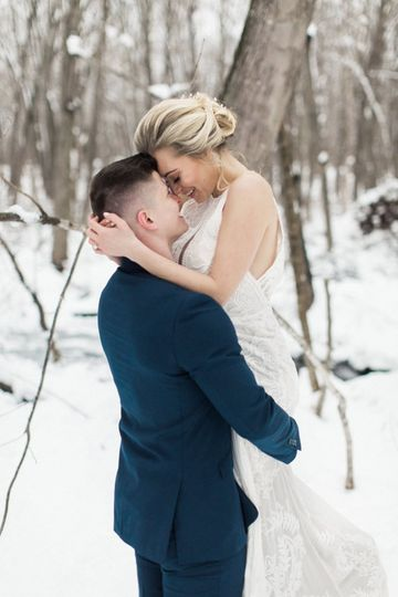 The newlyweds embrace in the snow