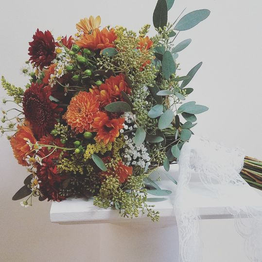 Fall bouquet with mums, baby's breath, hypericum berries and seeded eucalyptus.