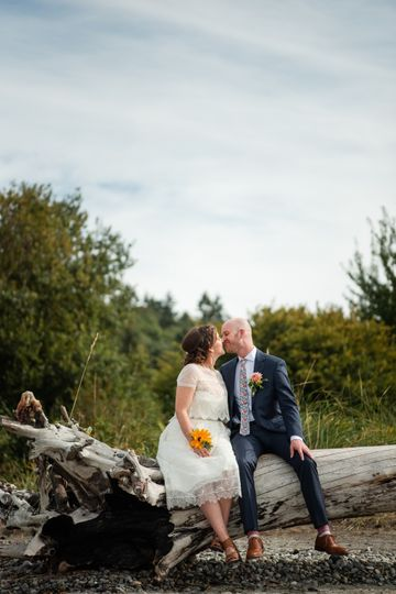Couple on log - beach wedding