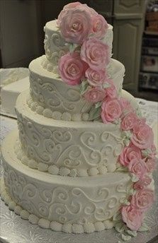 wedding cake with cascading pink roses and scrolls