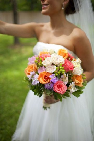 A beautiful summer bride carrying coral and ivory roses, stock, alstroemeria in a hand tied summer...