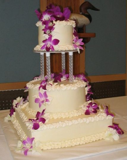Square and rounds make up this elegantly simple wedding cake adorned with fresh orchids