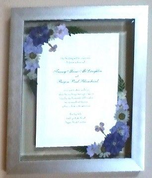 Wedding invitation mounted in brushed silver frame.