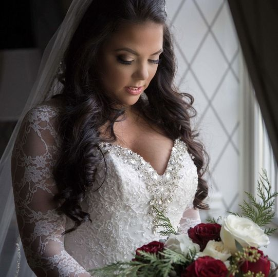 Bride in her makeup and in a sleeved lace wedding dress