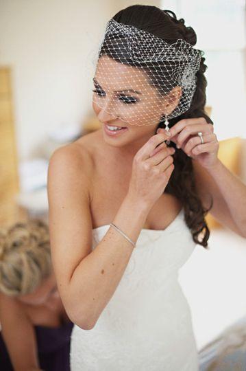 Happy bride putting in earrings