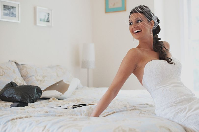 Smiling bride sitting on bed