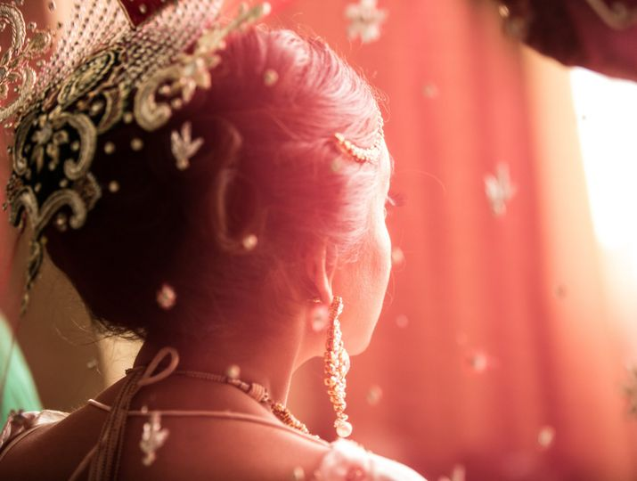 Indian bride's hair decorated with flowers, gold jewelry and the traditional red cloth