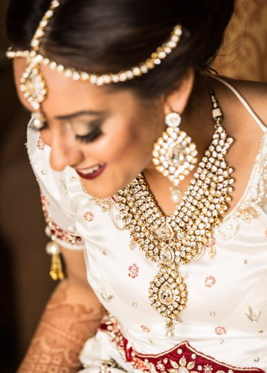 Gold jewelry - necklace, ear rings, head chains - is staple in Indian weddings